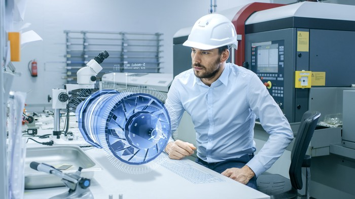 A man in a hard hat looks at a floating 3D object