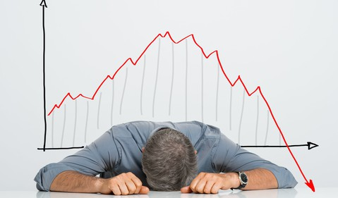 Man with head on table, stock chart crash in background