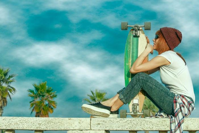 Skater girl sitting on a railing holding her board