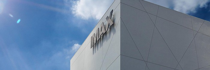 View of upper corner of outside of IMAX theater building, with blue sky above.