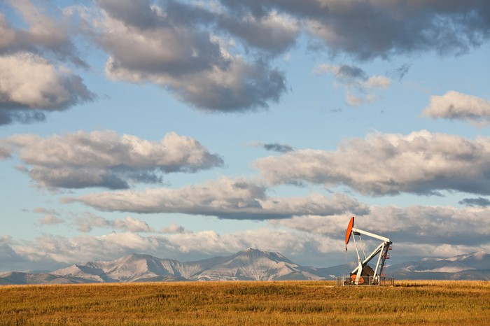 An oil pump in a field with the mountains in the background.