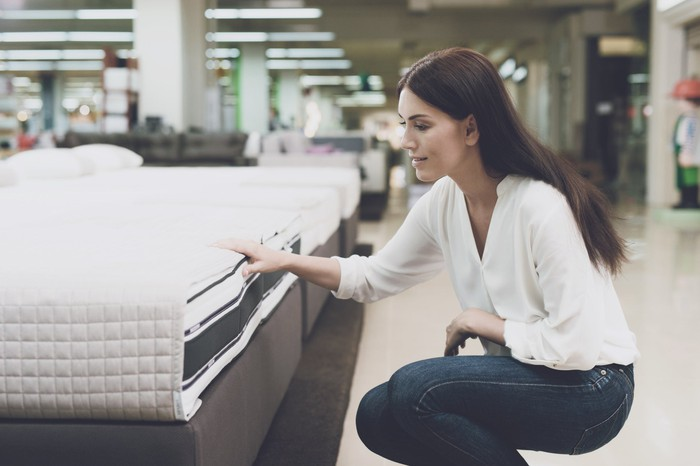 A woman touching a mattress in a mattress store.