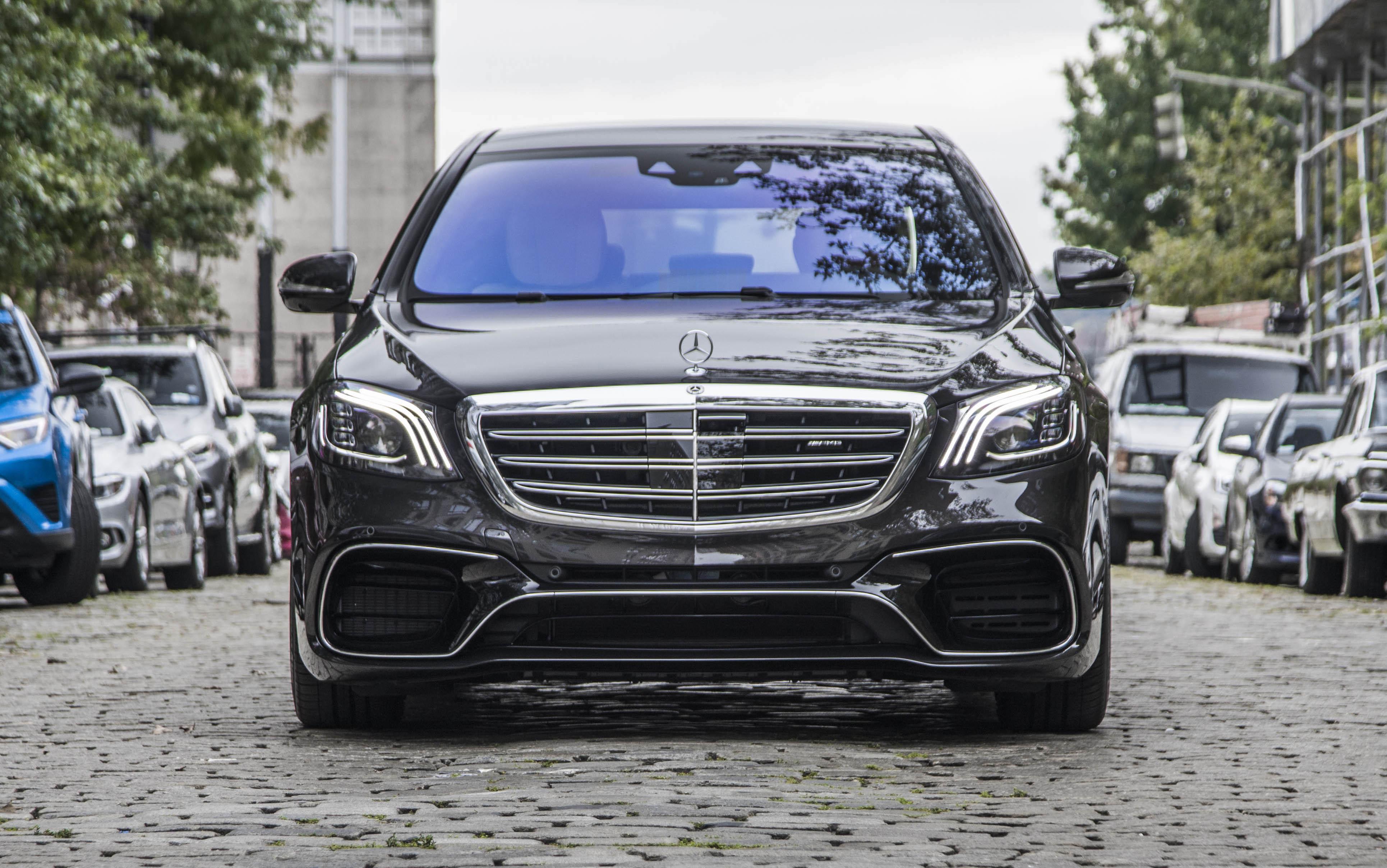 A black Mercedes-Benz S-Class sedan on a cobblestone street