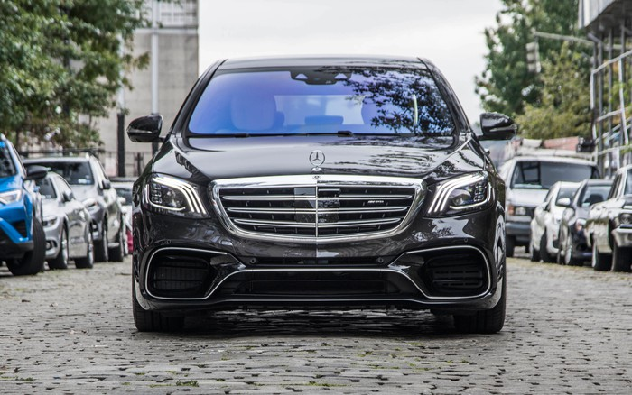 A black Mercedes-Benz S-Class sedan on a cobblestone street