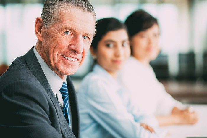 Smiling older man in suit sitting next to two younger female workers.