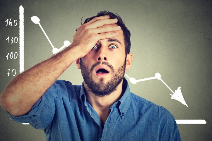 A man holds his forehead with his hand while standing in front of a wall showing a declining stock price chart.