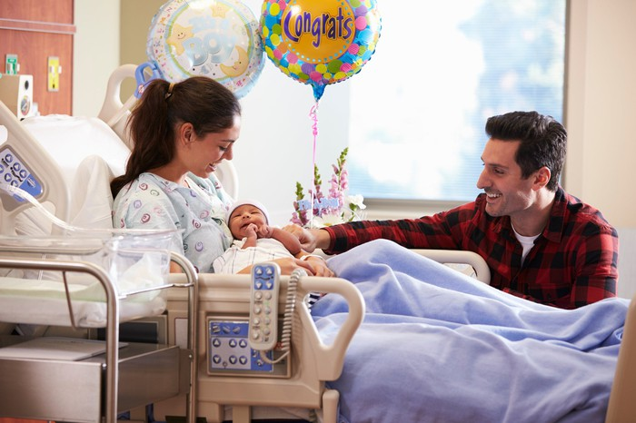 Infant in mom's arms in a hospital room with dad and baloons