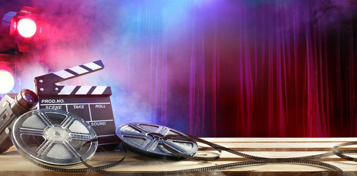 A clapperboard and film reels in front of smoke effects, a spotlight, and a theater curtain