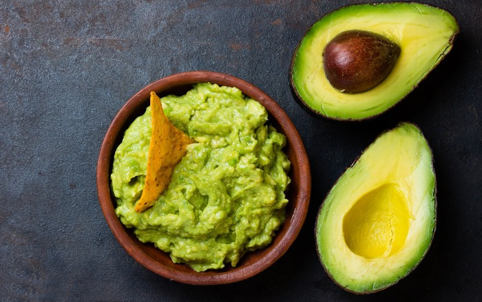 A bowl with guacamole and sliced avocados on a table.