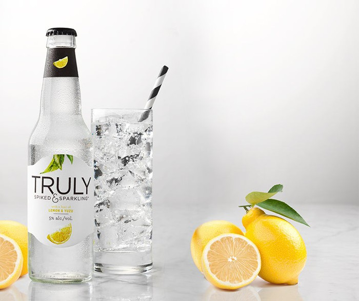 Truly brand of hard seltzer in a bottle and in a glass with a straw and next to lemons