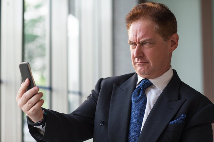 Man in suit scowling at his phone
