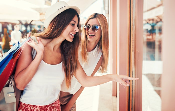 Two smiling women looking in a store window