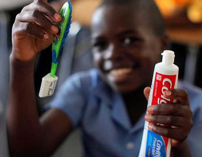 A boy holds up a tube of Colgate toothpaste and a toothbrush.