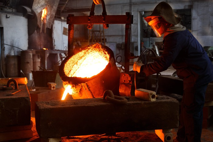 Worker pouring molten metal.