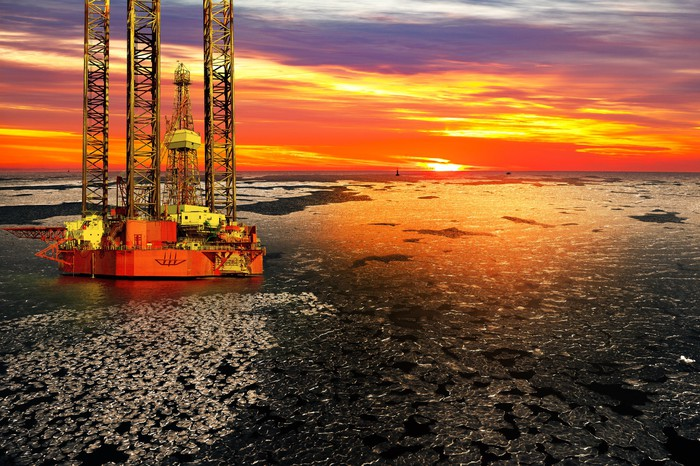 An offshore drilling rig with a bright sunset in the background.