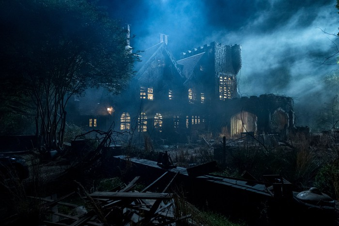 A Gothic house at night shrouded in fog.
