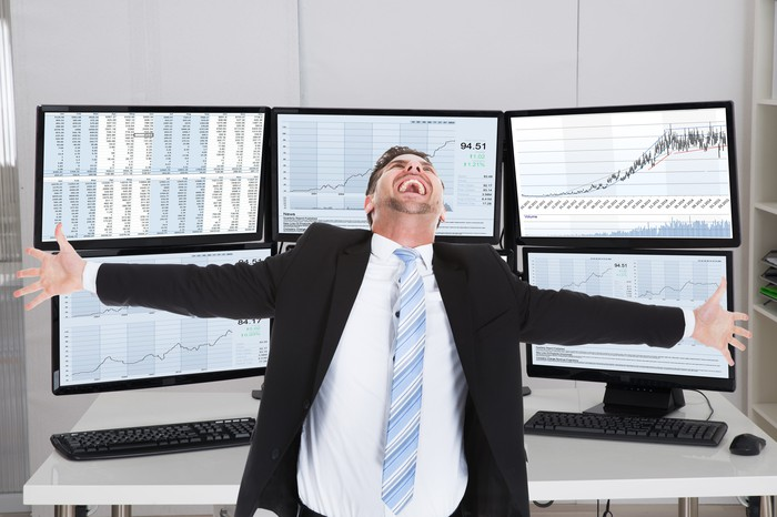 Exhilarated stock broker in front of computer screens.