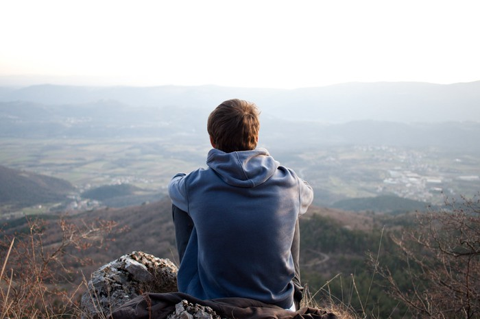 The back of a man sitting on a mountain side at looking at the horizon.