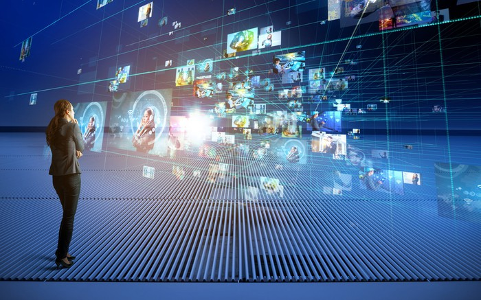 A woman watching multiple projections of digital advertising in front of her.