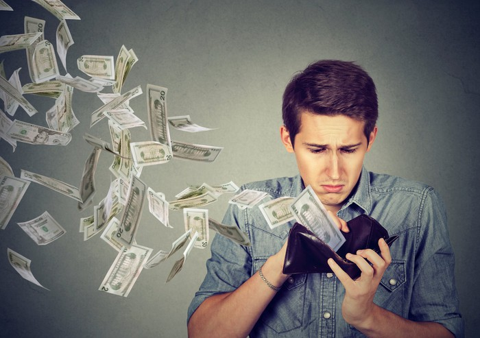 A young man looks sadly at his open wallet as paper American currency flies out.