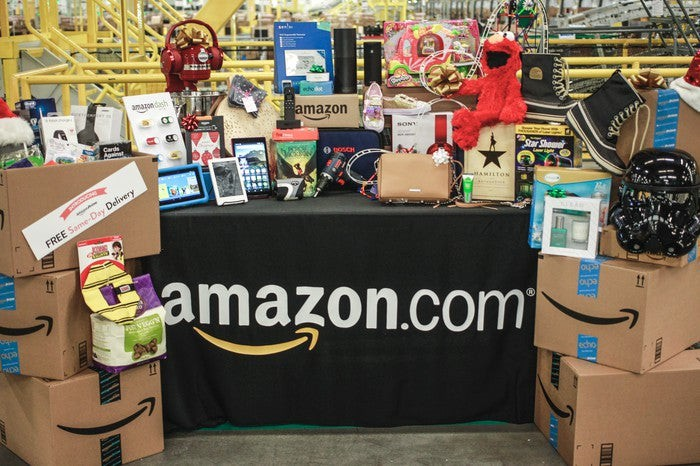 "Amazon packages and various unwrapped products available on its website sitting on and surrounding a table covered in a tablecloth that says ""amazon.com"" on the front."
