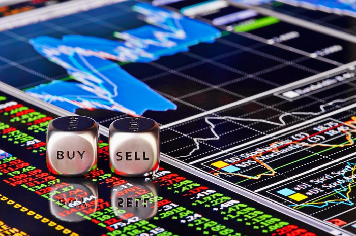 A pair of dice with the words buy and sell written on them rest on a digital financial chart.
