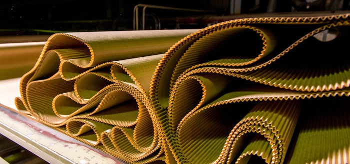 Wavy sheets of pleated carboard at a manufacturing mill.