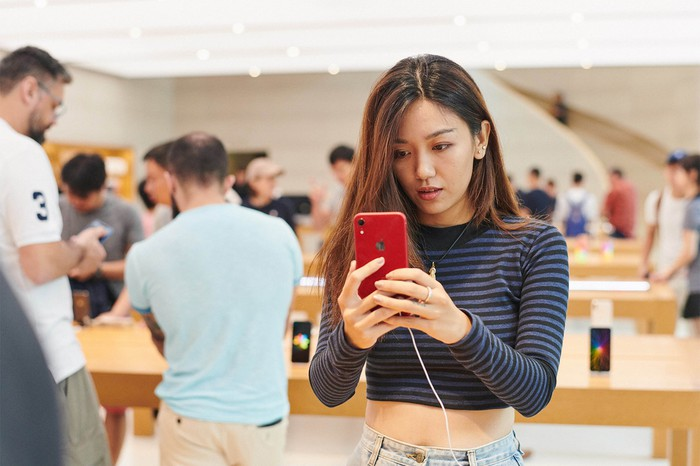 A young woman holding a red iPhone XR in an Apple Store.
