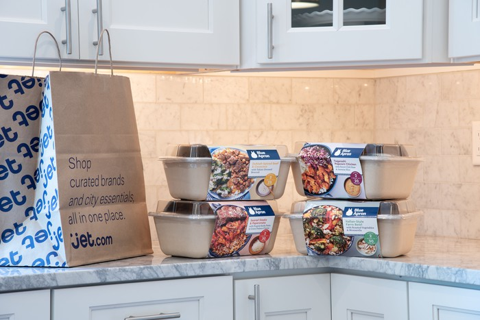 Blue Apron meal kits sitting on a counter next to a Jet.com bag.
