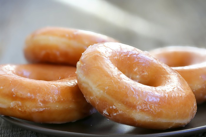 Glazed donuts piled on a plate.