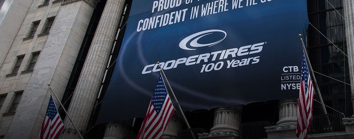 Banner with Cooper Tire logo and slogan hanging from New York Stock Exchange pillars.