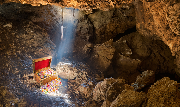 A single beam of light shines down on a treasure chast, overflowing with gems and gold, in a dark cave.