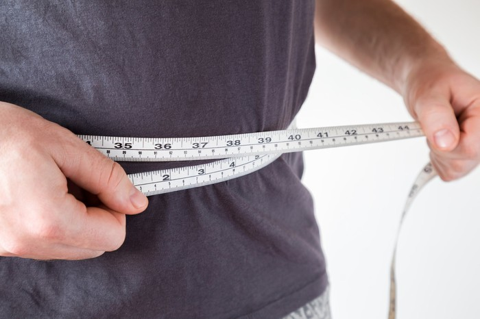 A measuring tape being held around a person's waist.