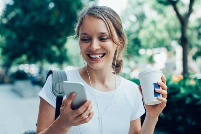 A young woman looks at her smartphone as she drinks coffee.