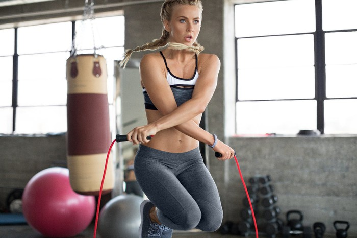 Julianne Hough donning a Fitbit as she jumps rope in a warehouse gym.