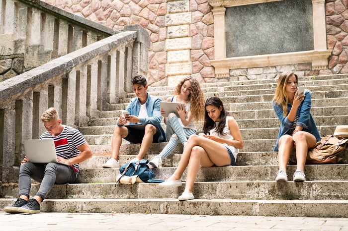 Teenagers with smartphones and computers sit on stone steps.