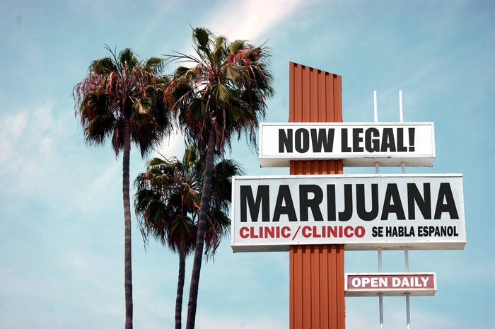 A sign for a marijuana store next to palm trees