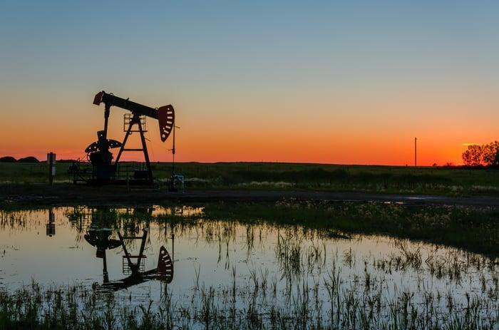 An oil pump next to a pond.
