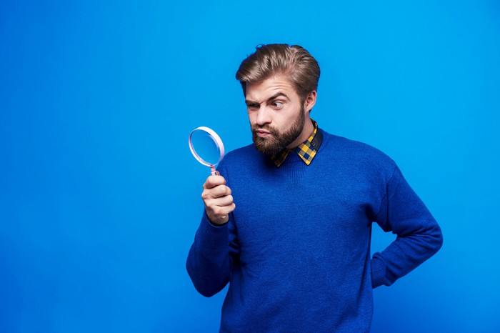 A bearded man looks into a magnifying glass with a raised eyebrow