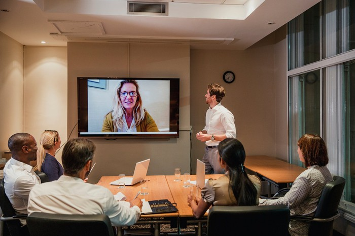 Professionally dressed adults in a conference room looking up at a woman videconferencing in on a large screen.