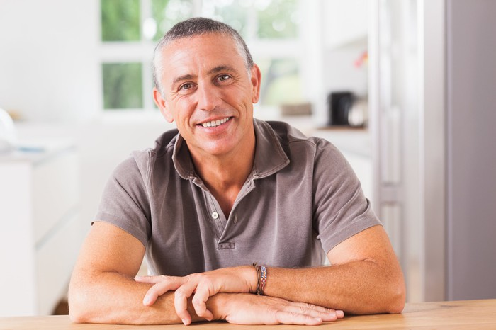 Smiling middle-aged man sitting down at table