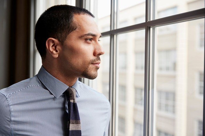 Professionally dressed man looking out a window