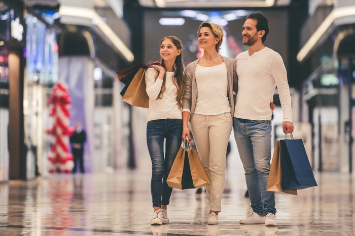 Family of three walking through a mall while carrying shopping bags.