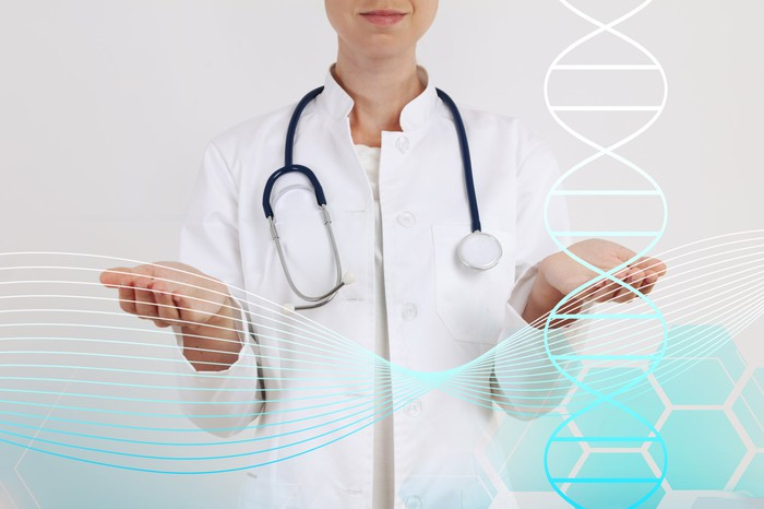 Doctor with stethoscope around her neck holding palms upward with image of a DNA helix in the foreground