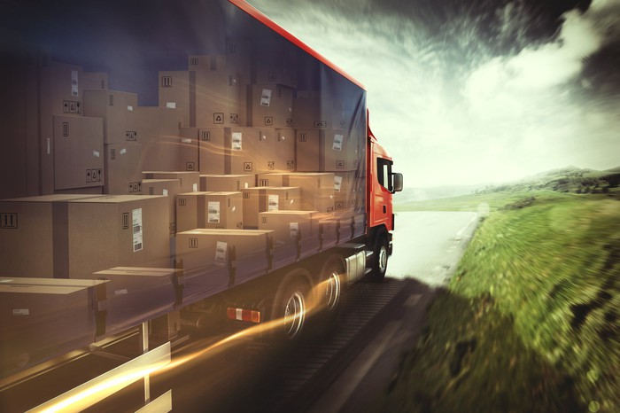 Photo-realistic illustration of a freight truck on highway, with packages exposed through a transparent side panel.