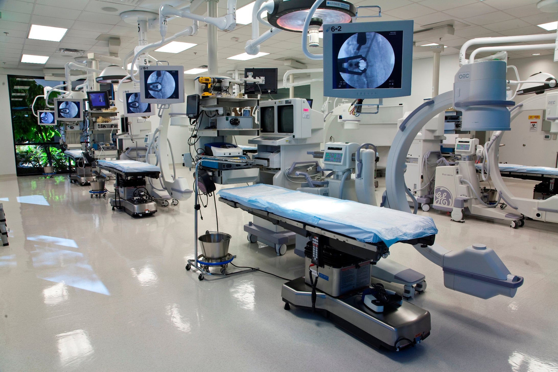 Several spinal surgical tables with imaging equipment and various monitors nearby, in a room with white tile floors and bright fluorescent lighting.