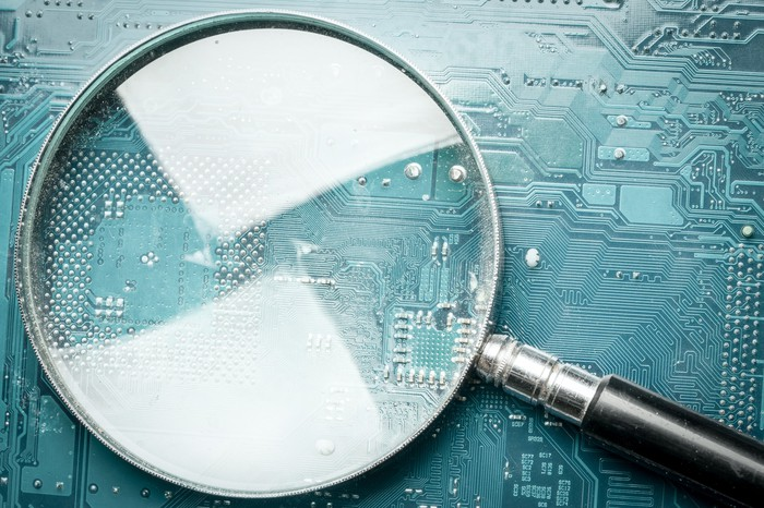 A magnifying glass laid on top of a circuit board.