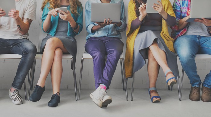 Young people using mobile devices while sitting on chairs lined up.