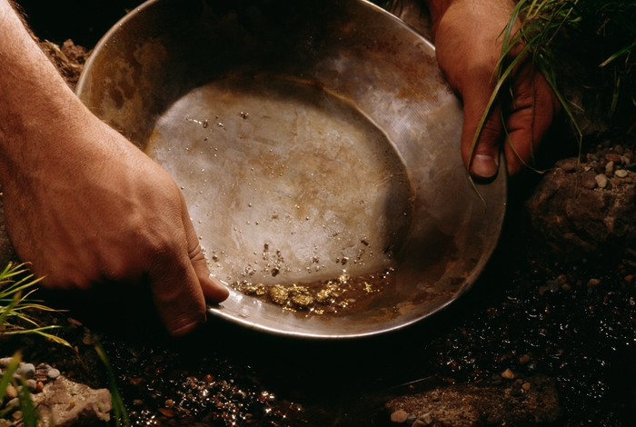 Close-up shot of two hands holding a pan and sifting for gold in a murky stream.