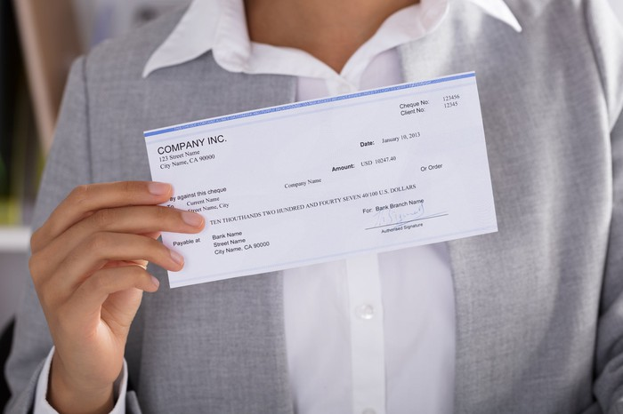 Woman with paycheck in her hand